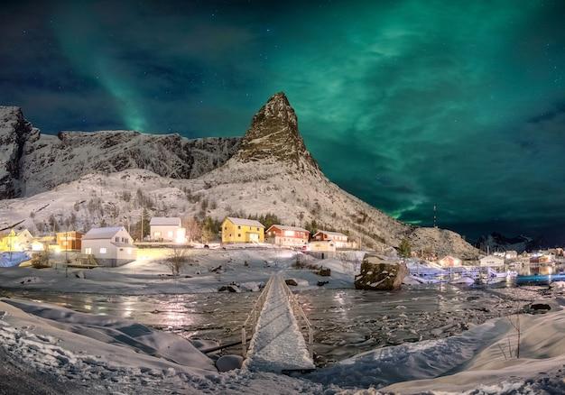 Panorama skandynawskiej wioski z aurora borealis nad ośnieżoną górą na lofotach, norwegia