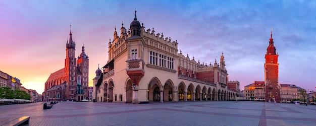 Panorama średniowiecznego rynku głównego z bazyliką mariacką, sukiennicami i wieżą ratuszową na starym mieście w krakowie o wschodzie słońca