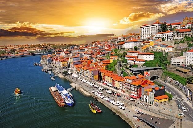 Panorama starego miasta porto nad rzeką duoro, z portem transportującym łodzie o zachodzie słońca, porto, portugalia