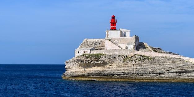Panorama starej czerwonej latarni morskiej phare de la madonetta na skale w pobliżu bonifacio corsica na tle