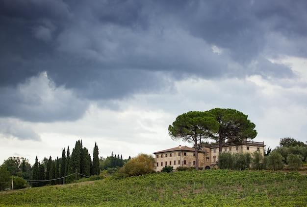 Panorama toskańskiego zbocza z zachmurzonym niebem i typową lokalną zabudową.