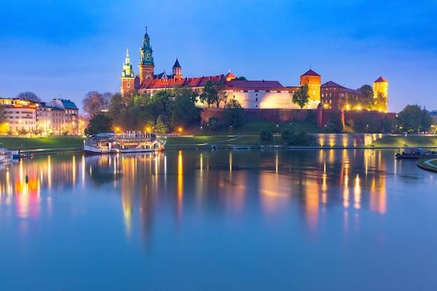 Panorama wawelu na wawelu z odbiciem w rzece w nocy, kraków, polska