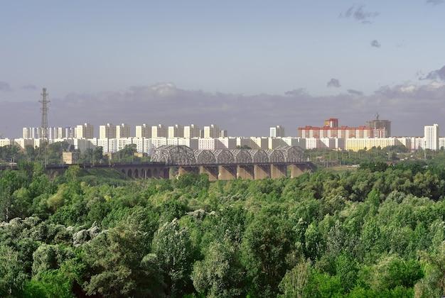 Panorama wielkiego miasta nowe wielopiętrowe budynki na horyzoncie most kolejowy