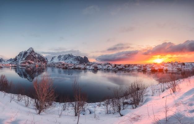 Panorama wschodu słońca na wiosce reine z odbiciem śnieżnej góry na wybrzeżu na lofotach