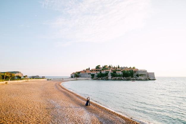 Panorama wyspy sveti stefan z zamkiem i parą spacerującą po brzegu