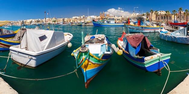 Panorama z tradycyjnymi kolorowymi łodziami luzzu w porcie w śródziemnomorskiej wiosce rybackiej marsaxlokk, malta
