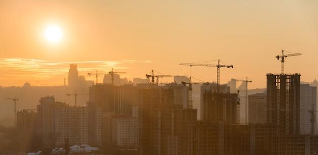 Panorama zachodu słońca w mieście z sylwetką budynków i przemysłowych dźwigów