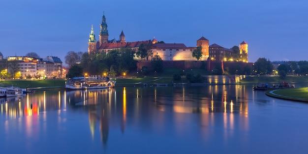 Panorama zamku na wawelu na wzgórzu wawelskim z odbiciem w rzece w nocy widziana z wisły, kraków, polska