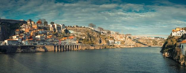 Panorama ze starymi domami rybackimi na wzgórzu obok kolejki linowej w dzielnicy ribeira nad brzegiem rzeki douro w mieście porto w portugalii