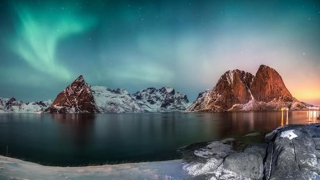 Panorama zorzy polarnej nad górą w wiosce rybackiej hamnoy zimą o wschodzie słońca