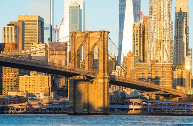 Panoramę manhattanu z mostem brooklińskim na pierwszym planie i wieżą wolności w tle.