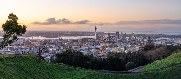 Panoramę miasta auckland z auckland sky tower z mt. eden o zachodzie słońca w nowej zelandii