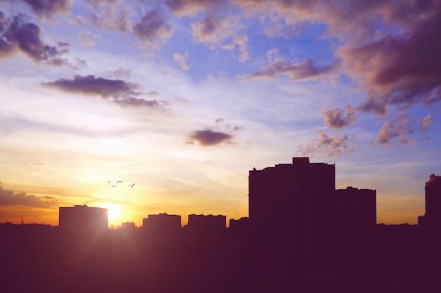 Panoramę miasta z sylwetkami budynków na niebie o zachodzie słońca