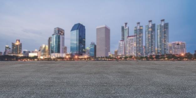 Panoramiczna pusta betonowa podłoga i linia horyzontu z budynkami