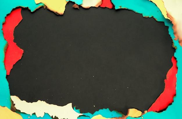 Panoramiczna ramka z spalonego papieru grunge z papierem w kolorze białym, żółtym, czerwonym z wypalonymi krawędziami.