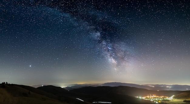 Panoramiczne nocne niebo nad santo stefano di sessanio, abruzzo i rocca calascio, włochy. galaktyka drogi mlecznej jest łukiem i gwiazdami nad oświetlonym krajobrazem unikalnych wzgórz wioski. widoczna planeta jowisz.