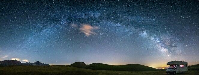 Panoramiczne nocne niebo nad wyżynami campo imperatore, abruzja, włochy. galaktyka drogi mlecznej i gwiazdy nad oświetlonym kamperem. kempingowa wolność w wyjątkowym krajobrazie wzgórz.