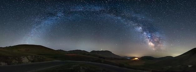 Panoramiczne nocne niebo nad wyżynami castelluccio di norcia, włochy. galaktyka drogi mlecznej jest łukiem i gwiazdami nad oświetlonym krajobrazem unikalnych wzgórz wioski. widoczna planeta jowisz.