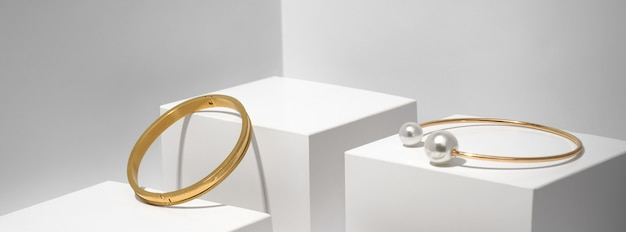 Panoramiczne ujęcie dwóch złotych bransoletek na białym tle geometrycznej