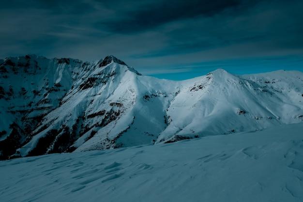 Panoramiczne ujęcie na szczycie pokrytej śniegiem góry pod zachmurzonym niebem