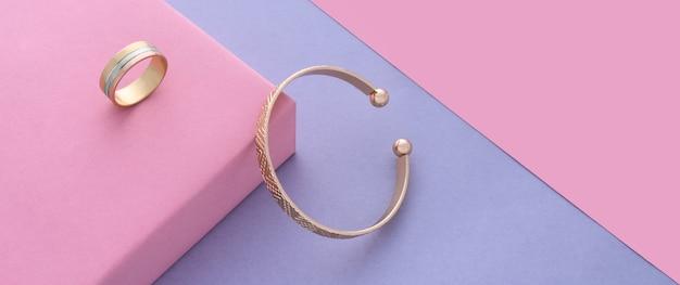 Panoramiczne ujęcie nowoczesnej bransoletki mankietowej i pierścionka na różowym i fioletowym tle z kopią przestrzeni