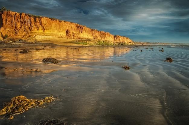 Panoramiczne ujęcie pięknego brzegu klifu w czasie odpływu pod zachmurzonym błękitnym niebem