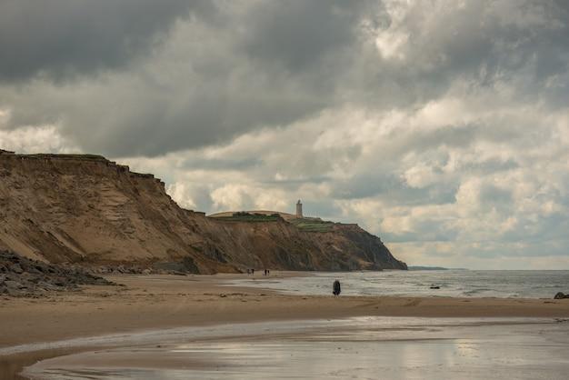Panoramiczne ujęcie skalistej góry i fal uderzających o brzeg w pochmurny dzień