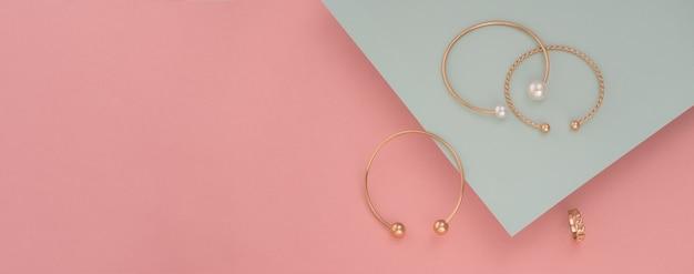 Panoramiczne ujęcie złote bransoletki na tle pastelowych kolorów z miejsca na kopię