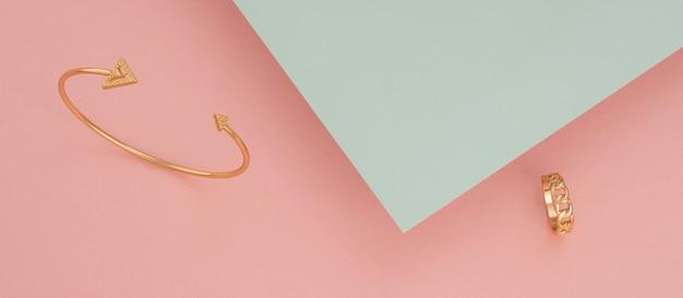 Panoramiczne ujęcie złotej bransoletki i pierścionka