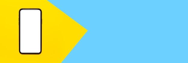 Panoramiczne zdjęcie smartfona z pustym ekranem na żółtej powierzchni