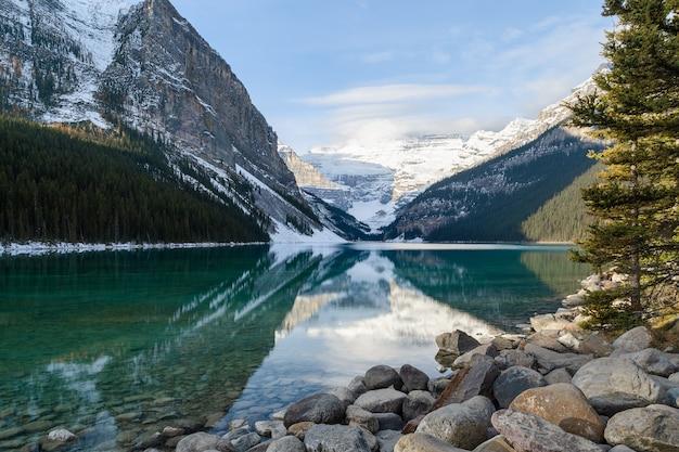 Panoramiczne zimowe góry odbicie w czystej wodzie nad jeziorem louise w parku narodowym banff w kanadzie