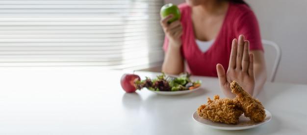 Panoramiczny baner. dieta. młoda ładna kobieta odmawia smażonego kurczaka, niezdrowego jedzenia lub niezdrowego jedzenia i jedzenia sałatki ze świeżego zielonego jabłka dla dobrego zdrowia w domu
