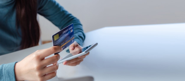 Panoramiczny baner. młoda kobieta, wprowadzając kod bezpieczeństwa za pomocą inteligentnego telefonu komórkowego i płacąc kartą kredytową na biurku w domowym biurze