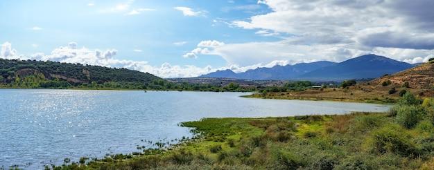 Panoramiczny górski krajobraz z dużym słonecznym jeziorem i małym miasteczkiem na brzegu.