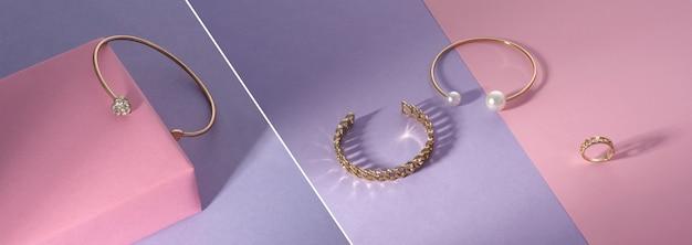 Panoramiczny kolaż zdjęć złotej biżuterii na różowym i fioletowym tle
