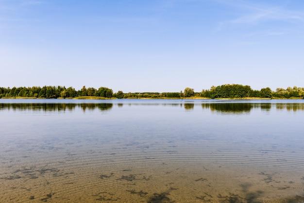 Panoramiczny krajobraz jeziora w południe z zielonym lasem w słoneczny letni dzień