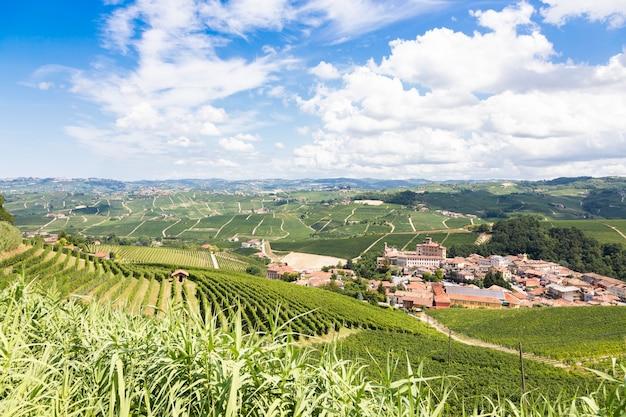 Panoramiczny krajobraz w regionie piemont, włochy. malownicze wzgórze winnic ze słynnym zamkiem i miastem barolo.
