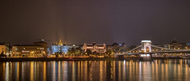 Panoramiczny krajobraz z pięknym nocnym widokiem na oświetloną historyczną część i most łańcuchowy przez rzekę w budapeszcie, węgry