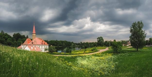Panoramiczny letni krajobraz z dramatycznymi chmurami i starym pałacem