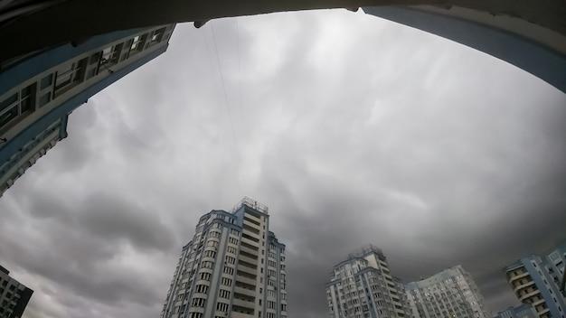 Panoramiczny obraz ciemnego nieba pokrytego szarymi i czarnymi chmurami deszczowymi nad wysokim budynkiem mieszkalnym w mieście. pejzaż miejski przed burzą