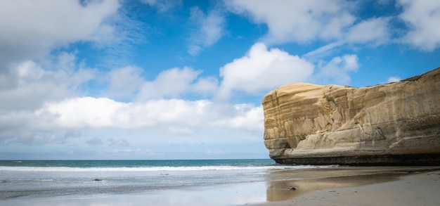 Panoramiczny pejzaż morski z błękitnym niebem i piaskowcową plażą w tunelu klifowym nowa zelandia