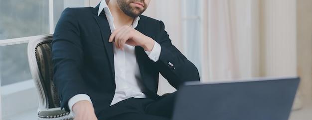 Panoramiczny portret biznesmena w garniturze, siedzącego na luksusowym krześle i patrząc w laptopa.