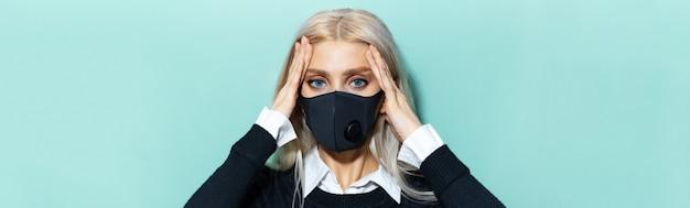 Panoramiczny portret młodej kobiety blondynka o bólu głowy, ubrana w czarną maskę medyczną na błękitnej powierzchni