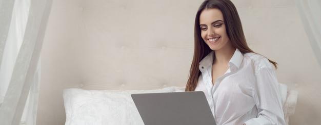 Panoramiczny strzał młoda uśmiechnięta dziewczyna pracuje na laptopie od domu