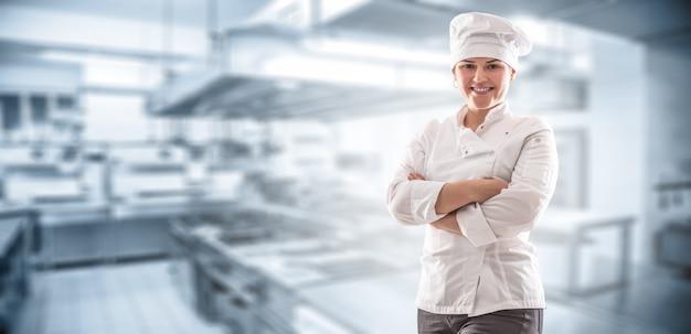 Panoramiczny sztandar szefa kuchni ze skrzyżowanymi rękami stojący przed kuchnią restauracji.