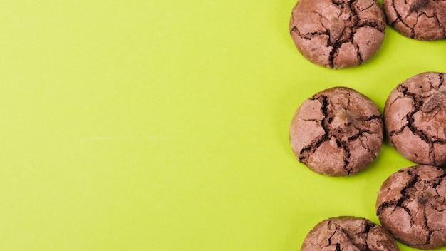 Panoramiczny widok czekoladowi ciastka na zielonym tle