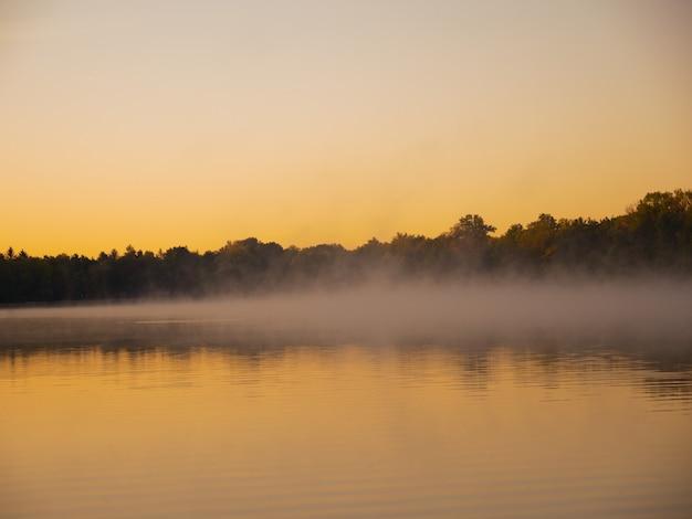 Panoramiczny widok mgły siedzącej na tafli wody o zmierzchu