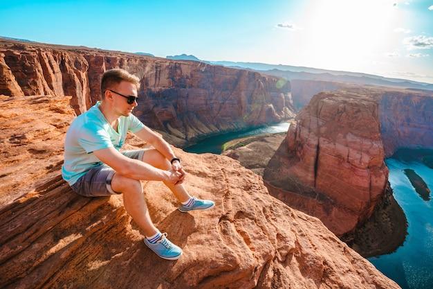 Panoramiczny widok młodego mężczyzny siedzącego na krawędzi klifu z widokiem na horseshoe bend w arizonie