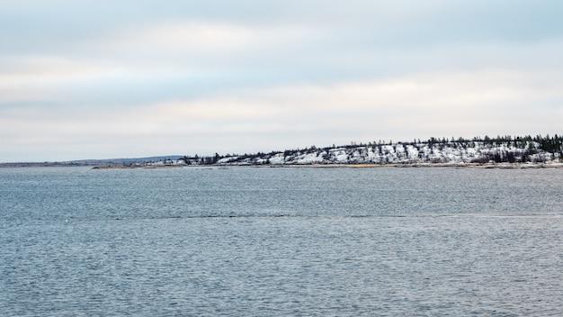 Panoramiczny widok na długi wąski kamień wystający z wody