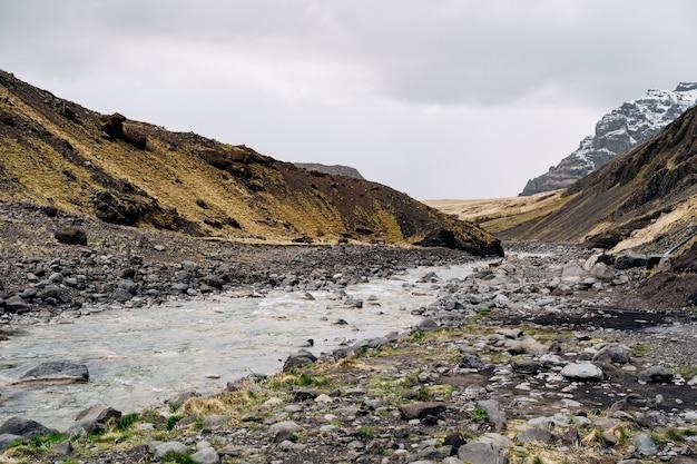 Panoramiczny widok na dolinę na islandii przez wąwóz przepływa płytka górska rzeka